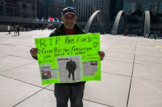 Jeff Walcott holds up a sign he made at City Hall for the late Rob Ford ahead of the funeral procession on Wednesday.